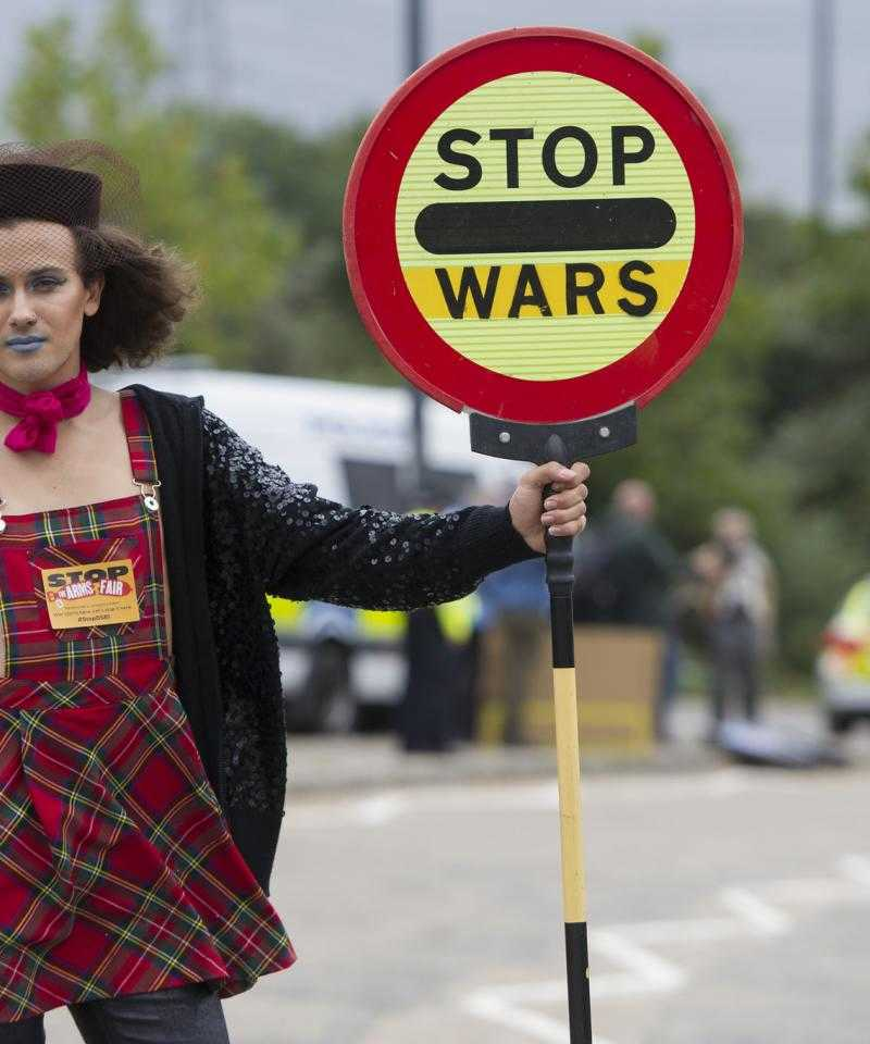 "A person holds a street sign reading ""stop wars"""