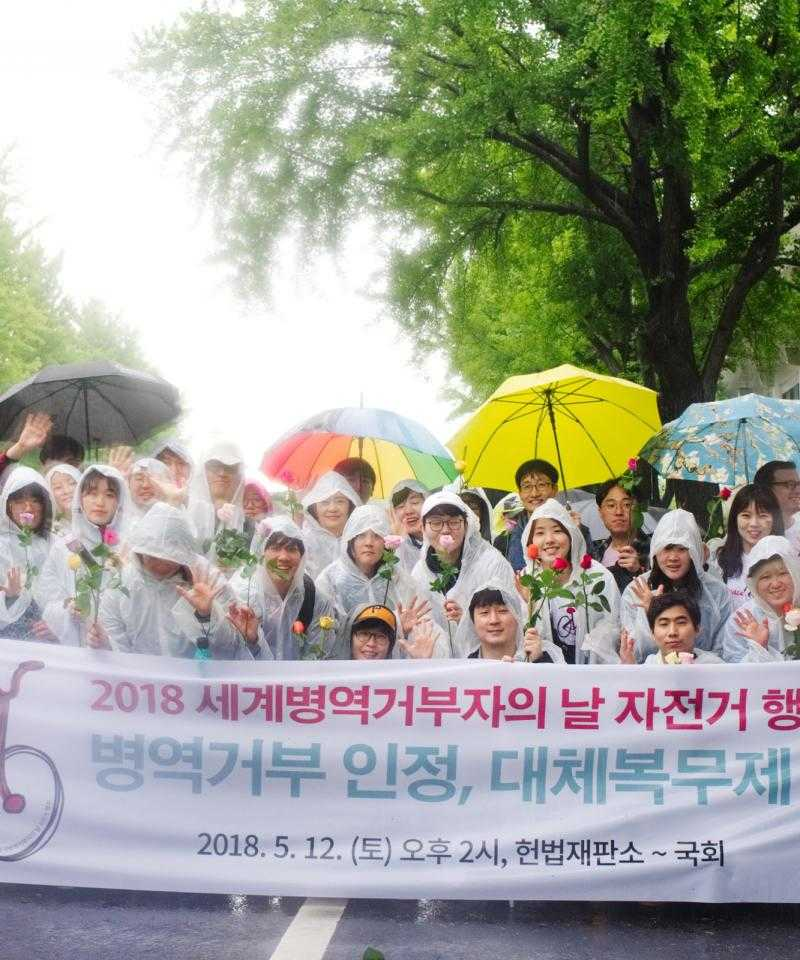 Activists in South Korea holding umbrellas and a banner