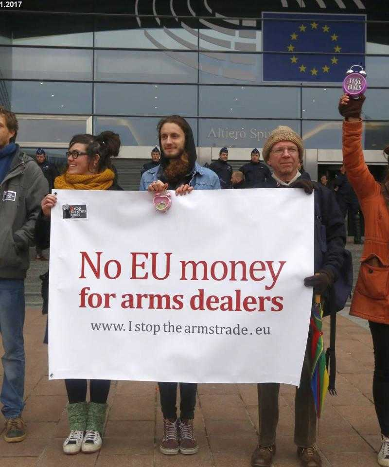 "A line of campaigners stand with a banner reading ""No EU money for arms dealers"", in front of a building flying the EU flag"