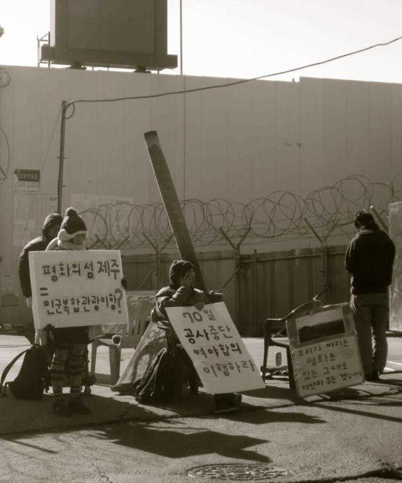 A blockade at Jeju Naval Base - activists stand in front of the gates with signs.
