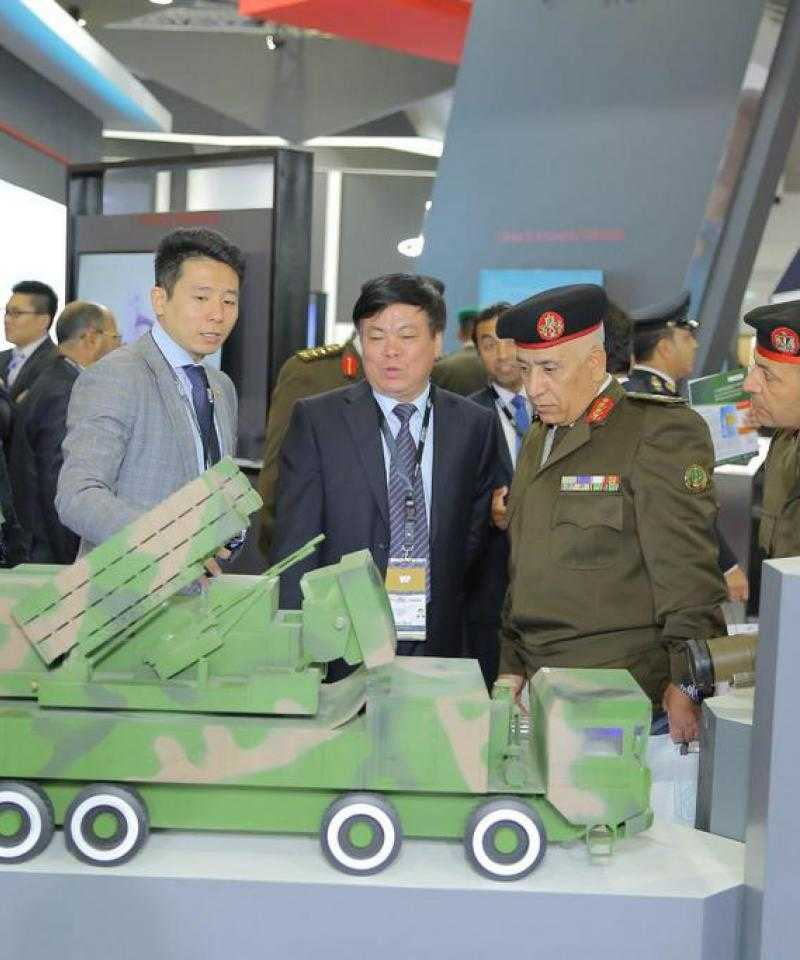 Several people - some dressed in military fatigues, others in suits - gather around a model tank