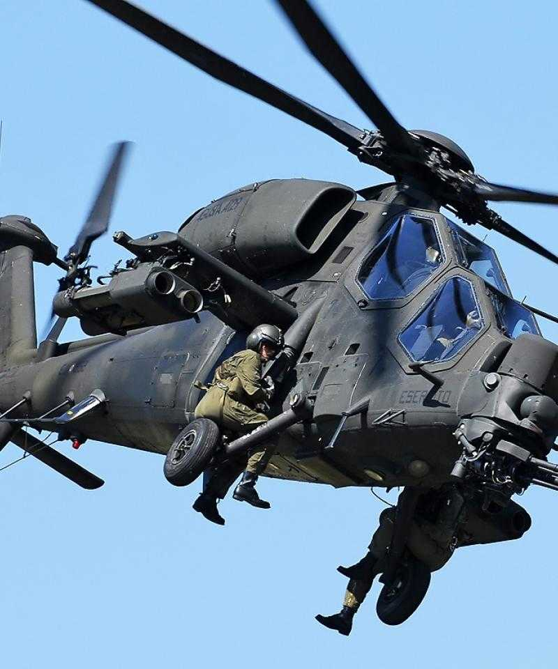 A military helicopter in flight. Two military personnel are sat on the outside.