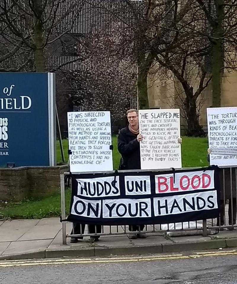 Four protesters hold signs outside the University of Huddersfield. The placards detail human rights abuses at the Bahrain Royal Academy