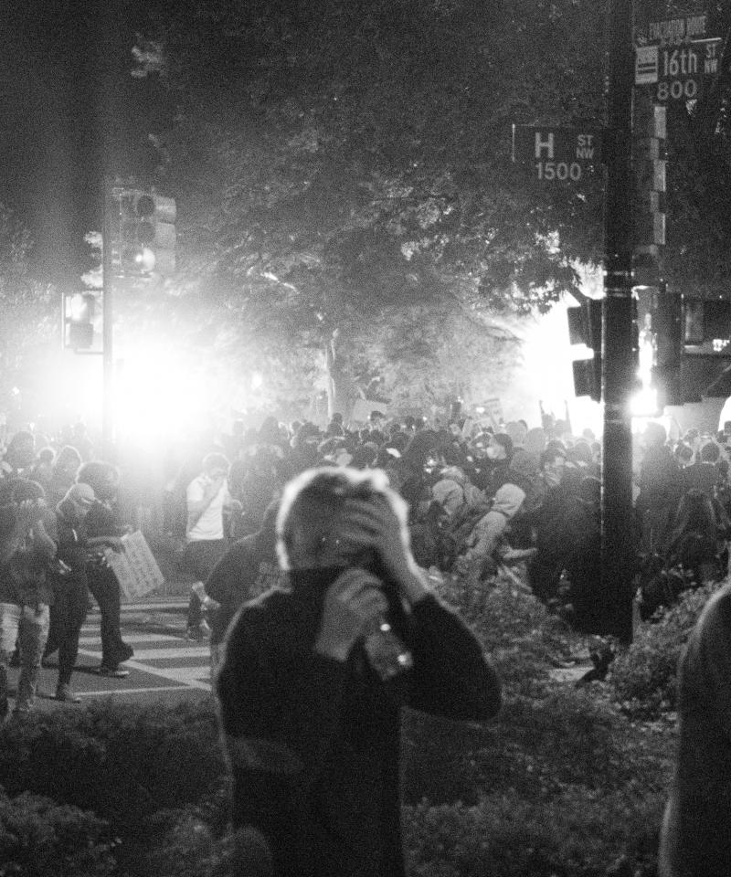 A black and white photo at night, showing large numbers of people walking through smoke with their mouths covered