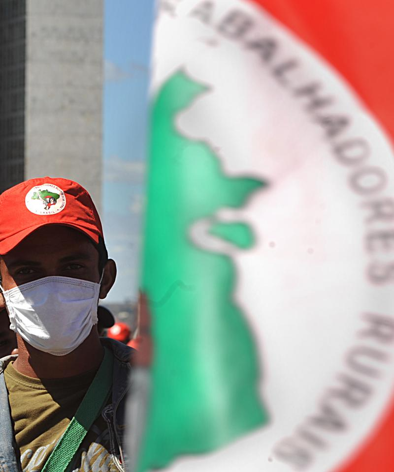 A man wears a mask while stood next beyind a red, green and white MST flag