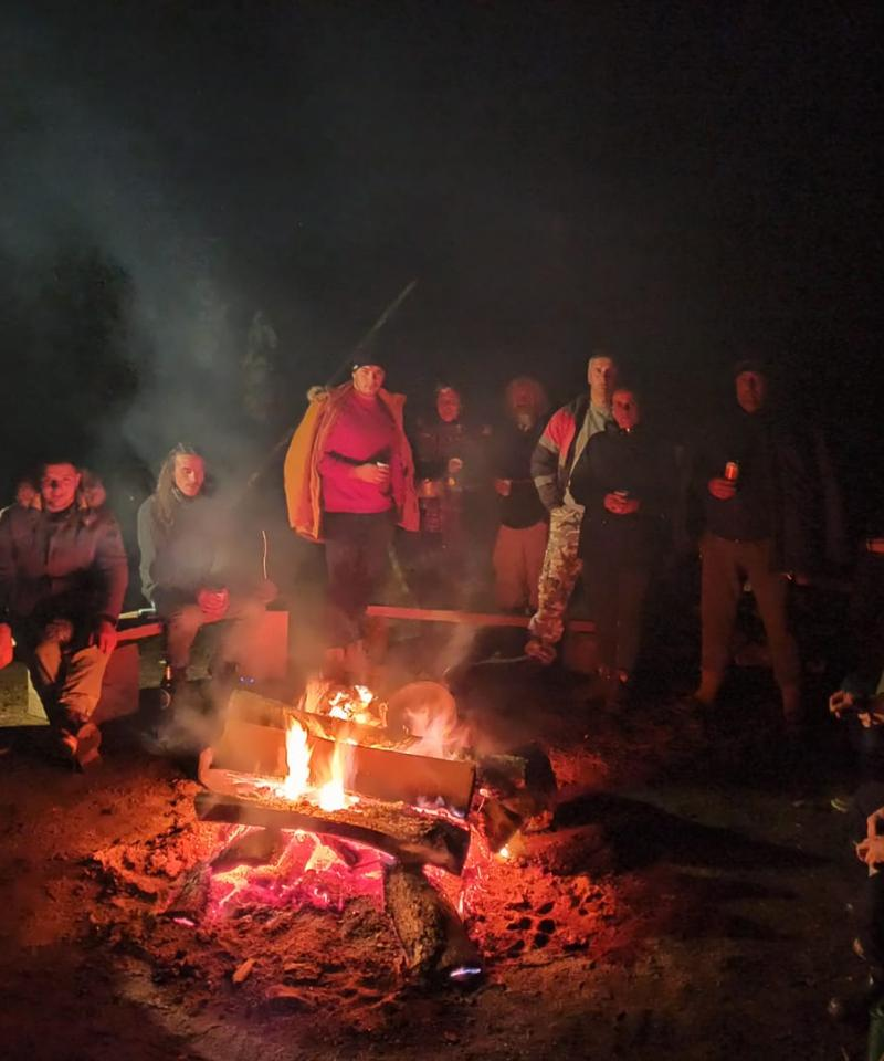 A large group of people sitting around a campfire at night