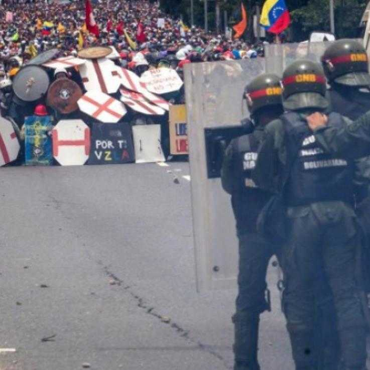 Police behind riot shields face a crowd of protesters behind a wall of homemade shields in Venezuela