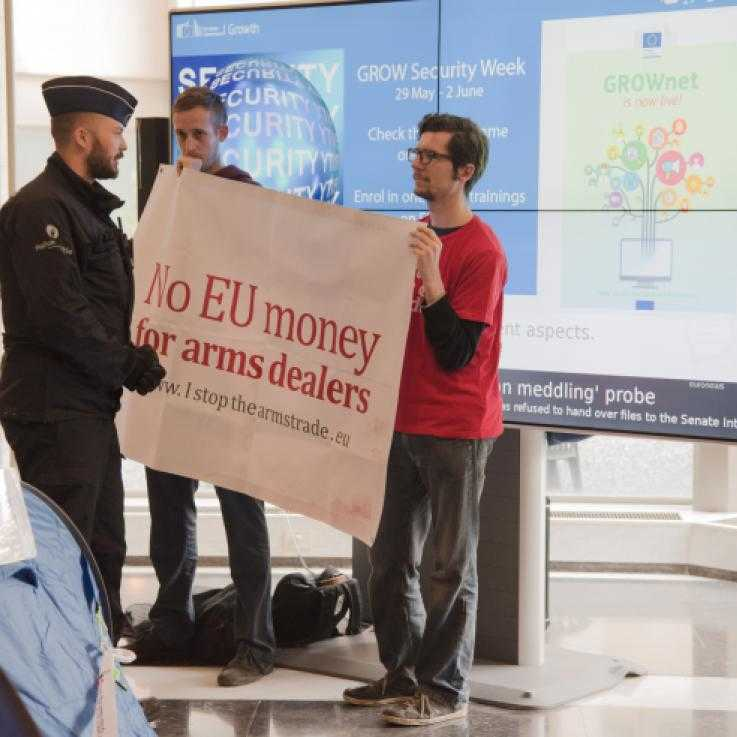 Protesters holding a sign reading 'No EU money for arms dealers' talking to police officers in the foyer of the European Commission