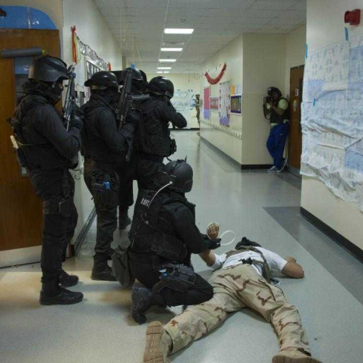 "A training exercise involving Bahraini and US police. A man being ""arrested"" is held to the floor while others point guns down a corridor. There is a photographer in the background."