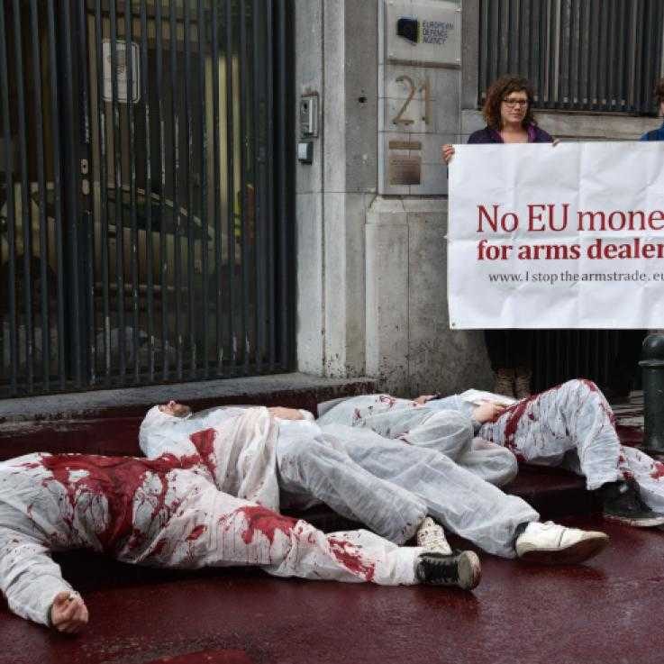 "Three activists dressed in white overalls lie in a pool of fake blood. Behind them stand two more activists holding a banner reading ""no money for arms dealers"""