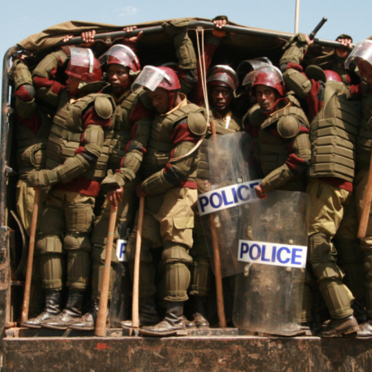 A large number of police armed with clubs wait to jump out of a van in Kenya. The police are wearing a lot of armour, shields, helmets and clubs.