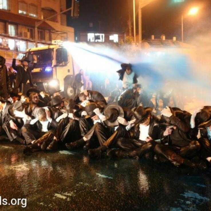 A police van sprays ultra-Orthodox demonstrators with blue liquid during a protest