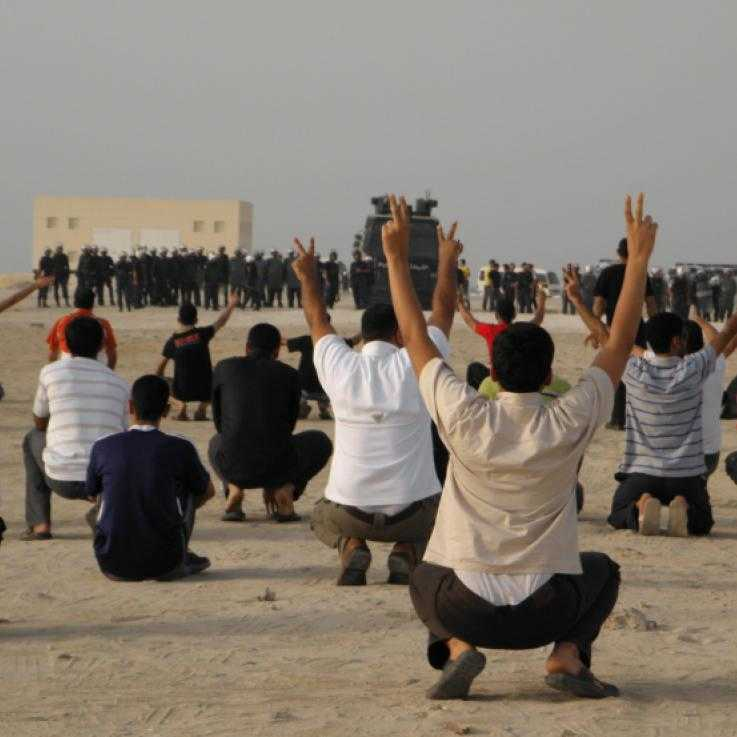Protesters squat in the foreground with their arms in the air making peace signs, their backs to the camera.  Facing them is a line of police dressed in riot gear with a large, armoured vehicle in the middle of the line.