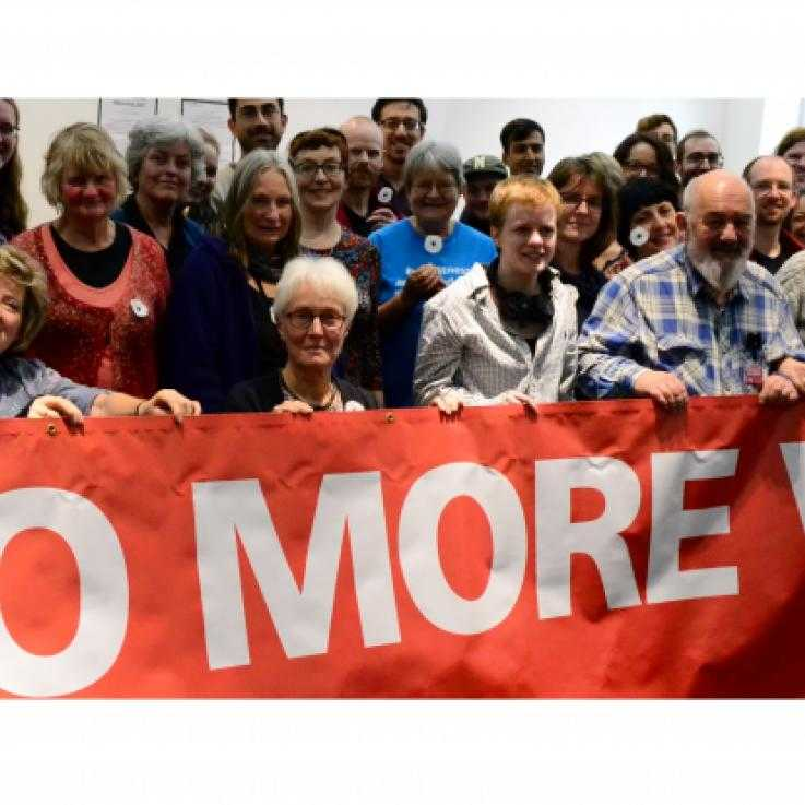 People holding a banner saying 'No more war'