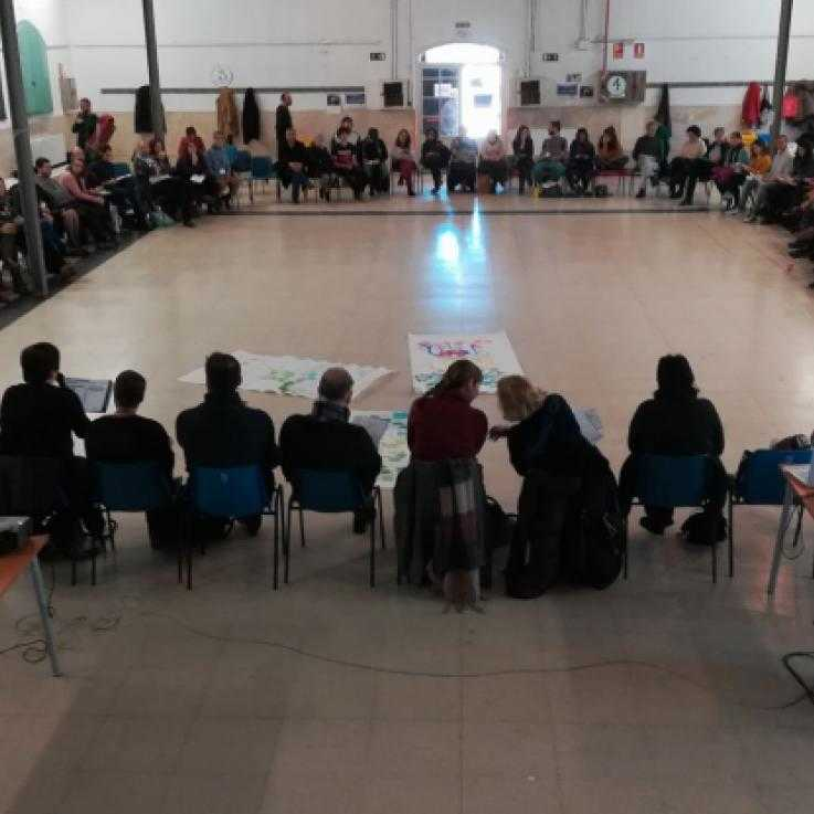 A large group of people sit in a large circle during the Noviolencia2018 congress