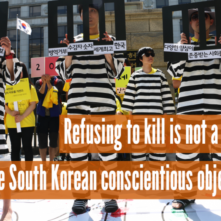 People standing holding signs that look like prison bars, with the text 'Refusing to kill is not a crime, Free South Korean conscientious objectors'