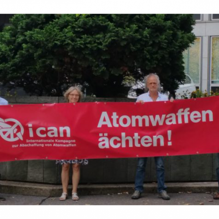 "Four people stand with a red banner reading ""Ban Nuclear Weapons"""