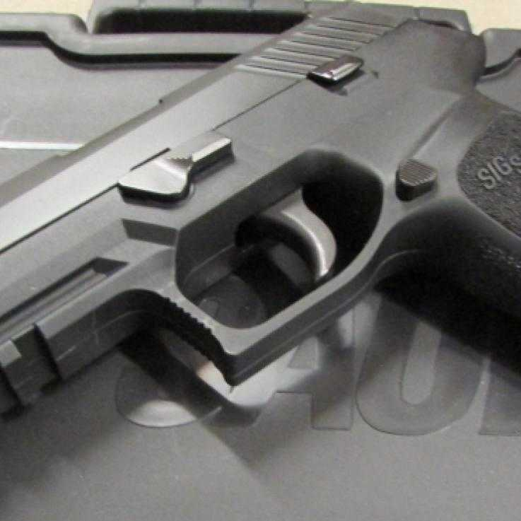 A Sig Sauer P320 pistol sat on a box
