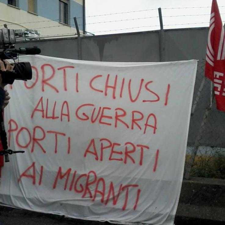 "A banner reading ""port closed to war, port open to migrants"" in Italian, hanging off a fence"