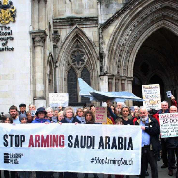 "A large crowd stand in front of the royal courts of justice. They are holding a banner with the words ""Stop arming Saudi Arabia"""