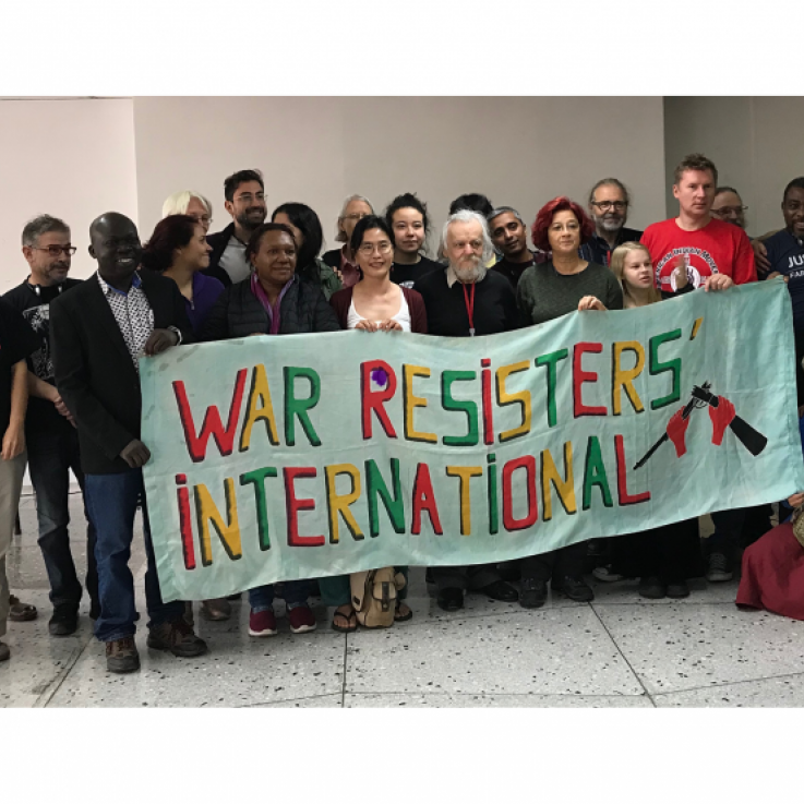 "Two dozen people stand behind a banner reading ""War Resisters' International"""