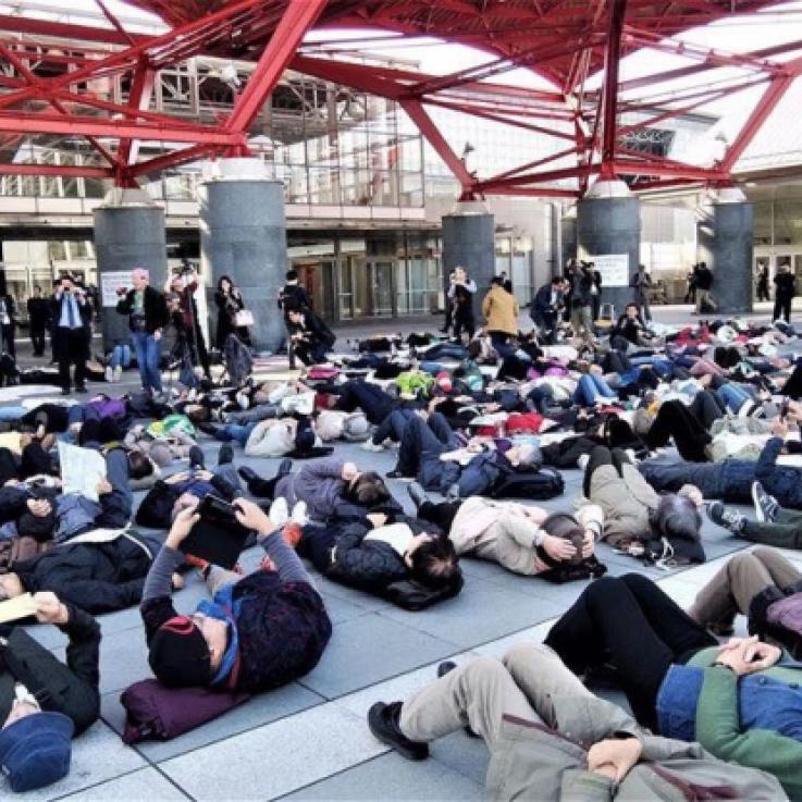 A large group of people take part in a die-in
