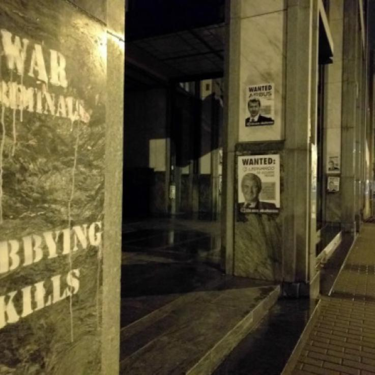 "Image taken at night. Grafitti saying ""Lobbying kills"" and ""war criminals"" alongside a Wanted poster"