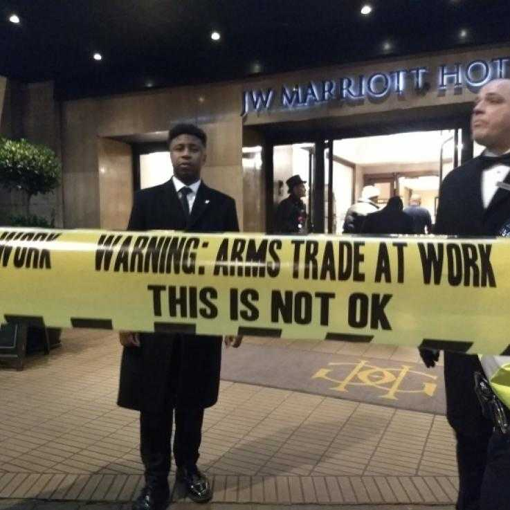 "Three security guards stand at the door of a hotel. In the foreground is some fake security tape reading ""Arms trade at work, this is not ok"""