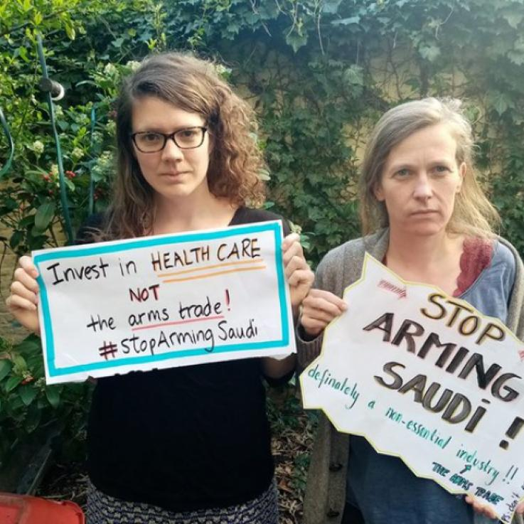 "Two people stand holding signs saying ""Stop Arming Saudi"""