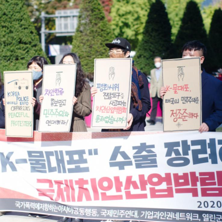 A number of Korean activists stand behind a large banner holding signs