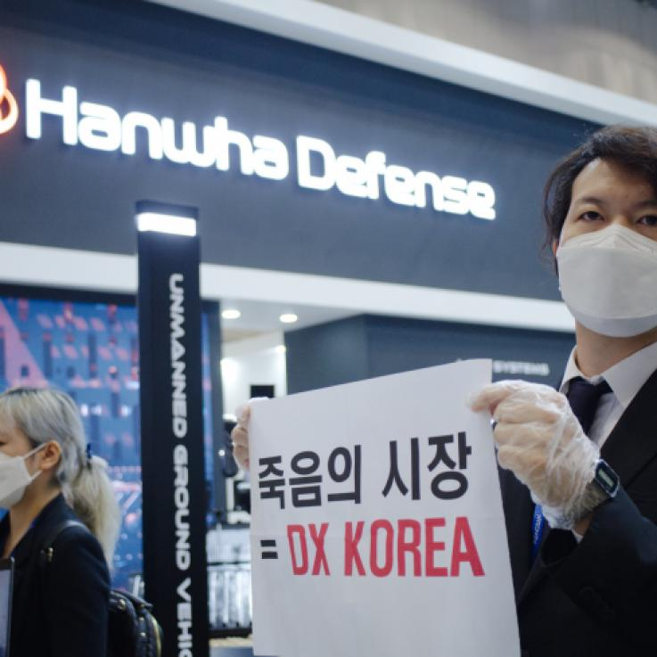 An activist dressed in a suit holds a protest sign in front of an arms exhibitor